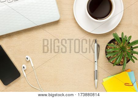 Top view notepaper pen cactus watch mobile phone paper clips Laptop earphones on office desk background.