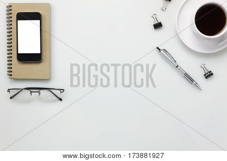 Top view accessories office desk concept.mobile phone coffee notepaper pen clip board on white office desk.