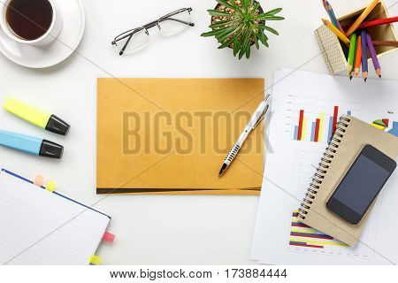 Top view accessories business office desk.mobile phone coffee notepaper pen letter colorful charted pencil eyeglasses on white office desk with copy space.