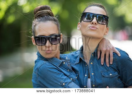Young beautiful twin sister with sunglasses in identical wardrobe posing in a park on a sunny summer day