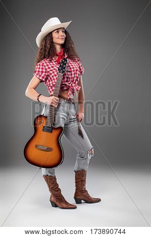 The cowgirl fashion woman with acoustic guitar over a gray studio background