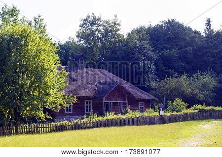 Old nice wooden house with wooden roof in village on summer warm day stands in shade in distance