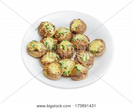 Baked button mushrooms stuffed with minced meat cheese and greens on the white dish on a light background