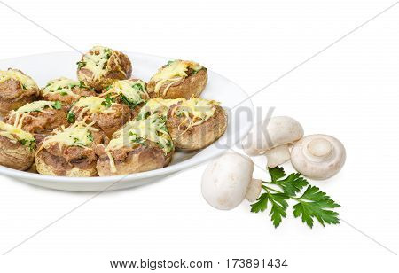 Baked button mushrooms stuffed with minced meat cheese and greens on the white dish and several uncooked mushrooms with parsley twig beside closeup on a light background