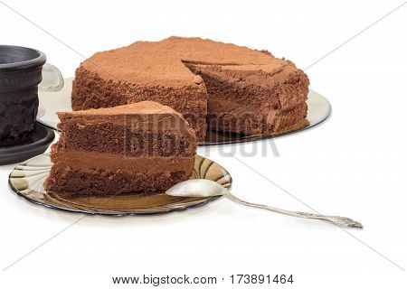 Piece of the chocolate layered cake sprinkled with cocoa powder and the spoon on a dark glass saucer on the background of the rest of the cake and coffee cup closeup on a light background