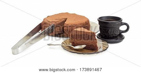 Partly sliced round chocolate cake sprinkled with cocoa powder on a glass dish and kitchen tongs piece of the cake with spoon on the glass saucer and coffee in the black ceramic cup on a light background