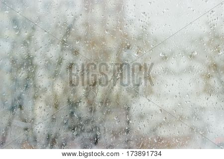 Background from a streams and drops of water on window pane and blurred tree through the glass during a rain in early spring