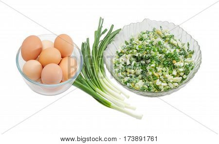 Spring salad with chopped green onions boiled eggs and sour cream in a glass salad bowl and separately the bunch of green onions and whole eggs in the glass bowl on a light background