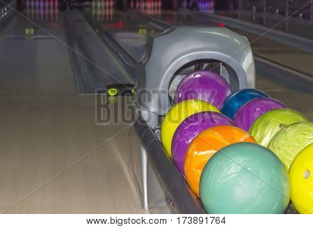 Colored bowling balls with a three finger holes closeup on the background of the blurred bowling lanes and bowling pins in a modern pin bowling alley