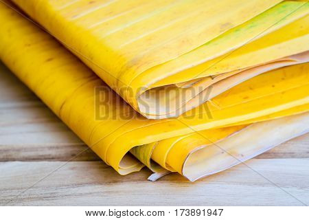 Yellow banana leaf on the wooden table