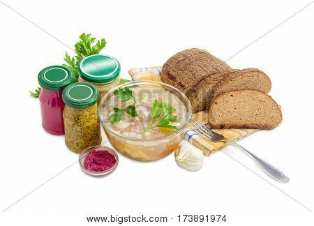 Pork aspic decorated with twigs of parsley in the glass bowl brown bread fork beet horseradish sauce mustard French mustard in small glass jars on a light background