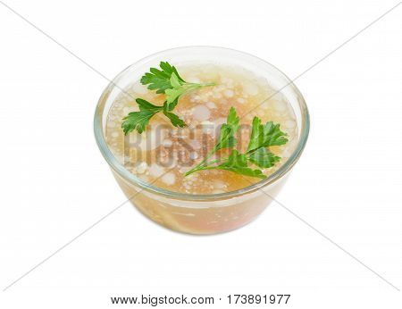 Pork aspic decorated with twigs of parsley in the glass bowl on a light background