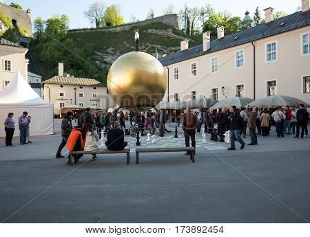 SALZBURG AUSTRIA - APRIL 29 2016: Stephan Balkenhol - Sphaera a sculpture of a man on a golden sphere on Kapitelplatz in Salzburg Austria