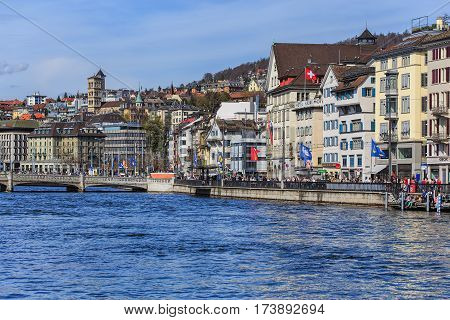 Zurich, Switzerland - 12 April, 2015: people on the embankment of the Limmat river during children's parade devoted to the upcoming Sechselauten holiday. The Sechselauten is a traditional spring holiday in the city of Zurich, children's parade.
