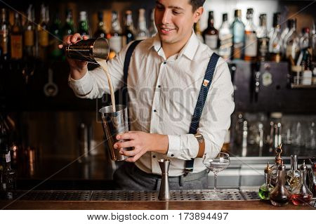 the bartender is smiling and mixing a coctail