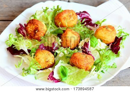 Small golden potato balls on a plate. Crispy potato balls with pumpkin seeds served with fresh salad mix and basil. Vegetarian potato recipe. Closeup