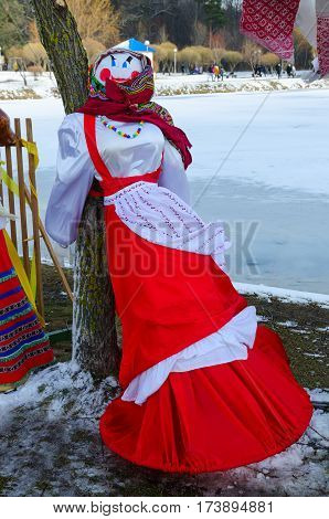 Pancake doll in colorful headscarf and sarafan near tree on bank of pond