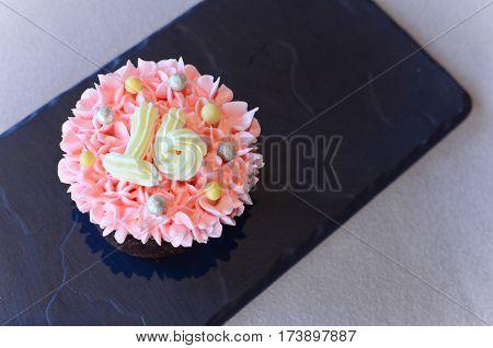 Closeup pink cupcake with number sixteen on top