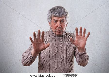 An irritated mature man with astonished and angry expression refusing something while showing no sign with his palms. Man wanting to stop something showing no gesture with hands.