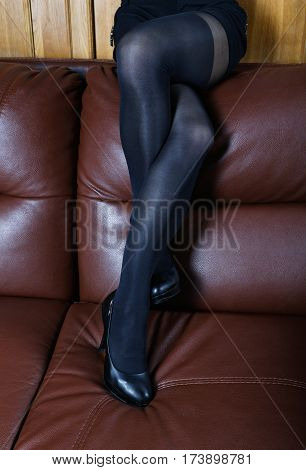 Female Feet In Black Stockings On A Leather Sofa