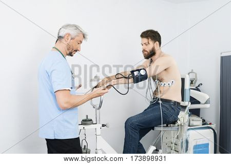 Doctor Checking Blood Pressure Of Patient Sitting On Exercise Bike