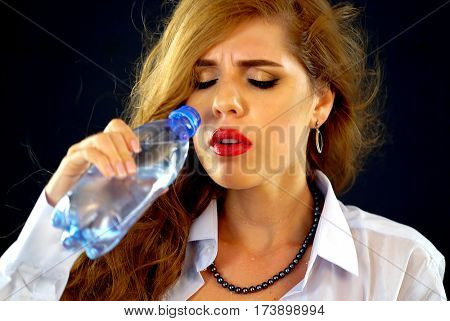 Sensitive teeth woman drinking cold water from bottle . Sudden toothache of thirsty girl in business suit drink . Painful facial expression. Lady with closed eyes guzzles on black background.