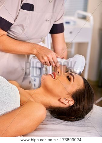 Ultrasonic facial treatment on ultrasound face machine. Woman receiving electric lift massage at spa salon. Electronic stimulation female muscles. Professional equipment microcurrent therapy .