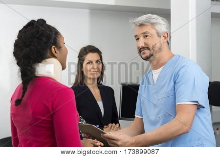 Injured Patient Consulting Doctor At Reception Desk