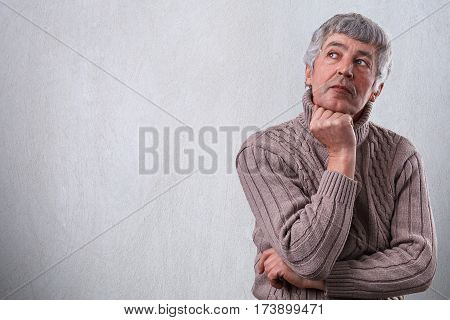 A horisontal portrait of senior man having serious face dreaming about something looking aside holding his hand under his chin. Thoughtful elderly guy. Great life experience. Composure and wisdom.