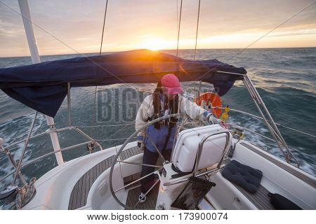 Man Standing At Helm Of Yacht Sailing In Sea During Sunset