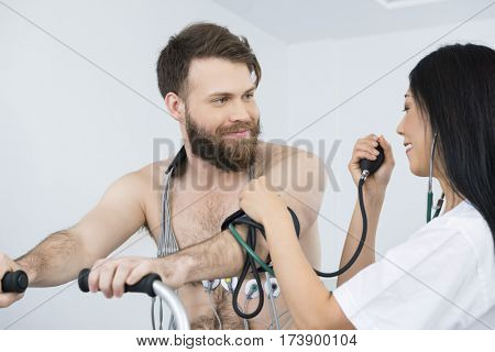Doctor Measuring Blood Pressure Of Patient With Electrodes On Bo