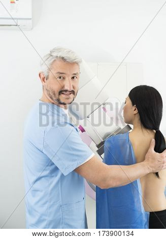 Doctor Assisting Woman Undergoing Mammogram X-ray Test In Hospit