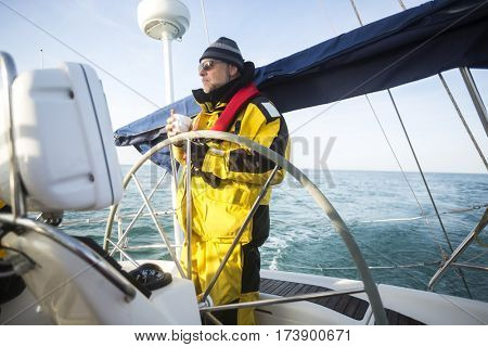 Man Holding Coffee Cup While Standing At Helm Of Yacht