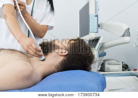 Patient Undergoing Ultrasound Of Thyroid From Doctor