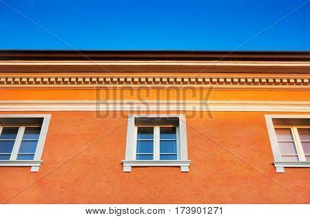 Historic orange colored house against blue sky