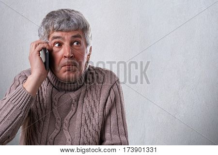 A pensioner talking over smartphone being astonished to receive call. A surprised expression of mature man in sweater isolated over white background holding cell-phone in his hand.