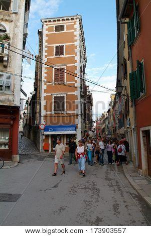 People Walking In The Narrow Alley Of Rovinj