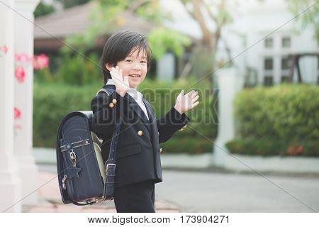 Asian student going to school and waving goodbye