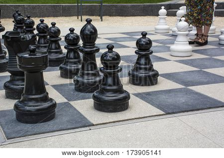 Black and white street chessmen with womans legs on the street chessboard