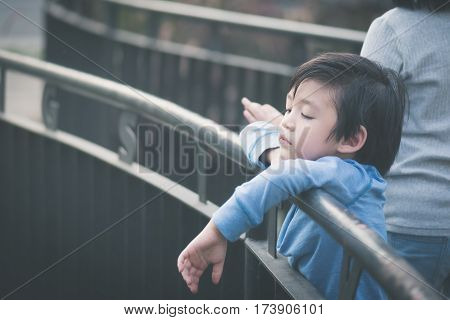 Close up cute Asian child feeling bored outdoors