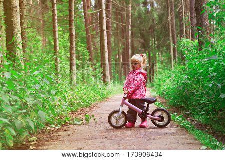 cute little girl riding bike in summer forest