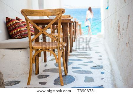 Benches with pillows in a typical Greek bar in Mykonos town with sea view, Cyclades islands, Greece