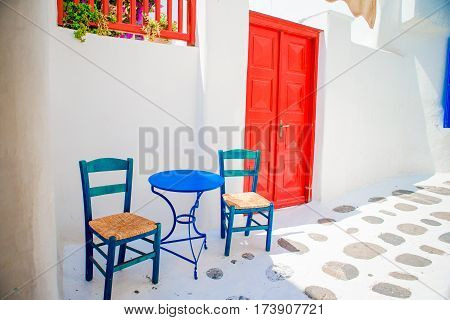 Colorful chairs and table on street of typical greek traditional village with white houses on Mykonos Island, Greece, Europe
