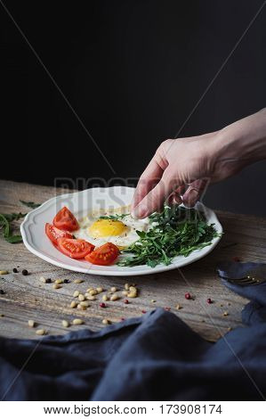 Breakfast with fried egg, green salad and fresh tomatoes. Female hand decorating plate with breakfast. Selective focus, rustic style