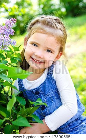 Portrait of smiling cute little girl outdoors on a summer day