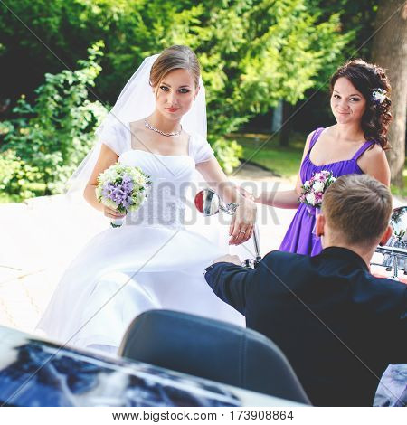 Bride impudently at a groom who sits on a motorcycle