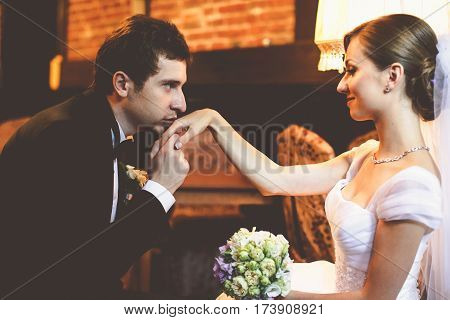 Handsome groom kisses the bride's delicate hand