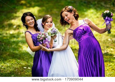 Gracious Bride And Bridesmaids Tries To Bend Over Standing On The Field
