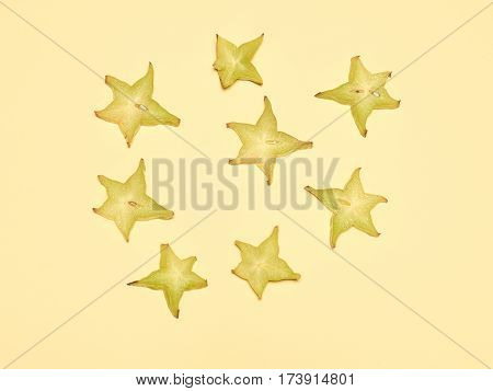Stacked slices of star fruit or karambole on a yellow background