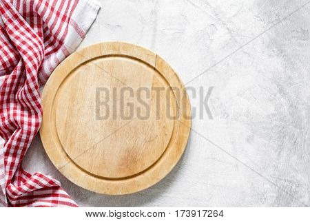 Old round wooden cutting board (pizza board) over bright gray stone background and classic red checkered tablecloth. Copy space for text. Cooking food, pizza, kitchen utensils background